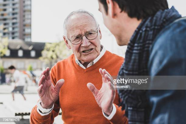 Senior man talking to adult grandson outdoors
