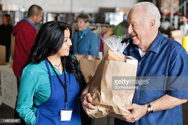 senior man talking to food donation volunteer - food bank stock pictures, royalty-free photos & images
