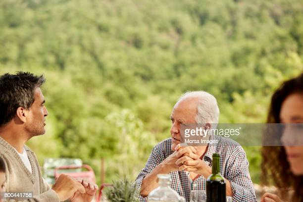 senior man talking to son at table during lunch - senior lunch stock photos and pictures