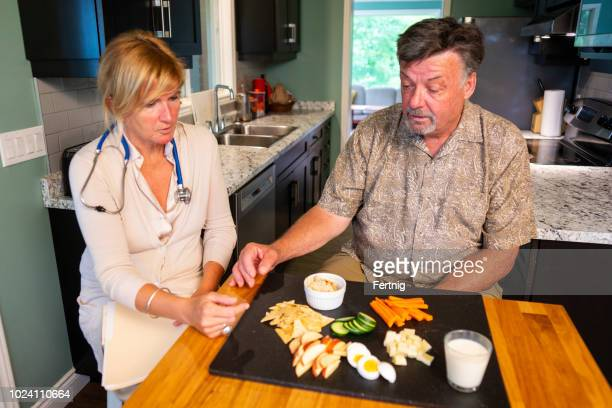 a senior man talking with a visiting nutritionist at home - nutritionist stock pictures, royalty-free photos & images