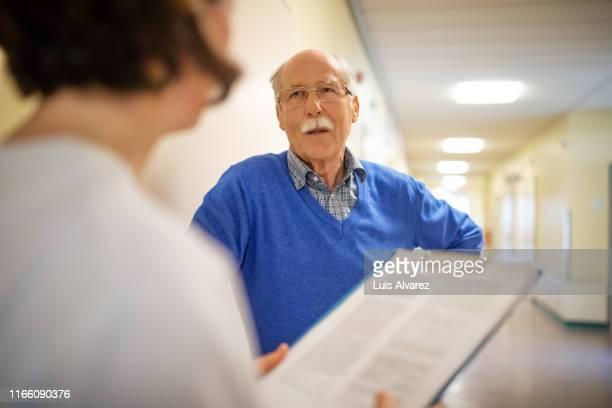 senior man talking with doctor in hospital hallway - medicare stockfoto's en -beelden