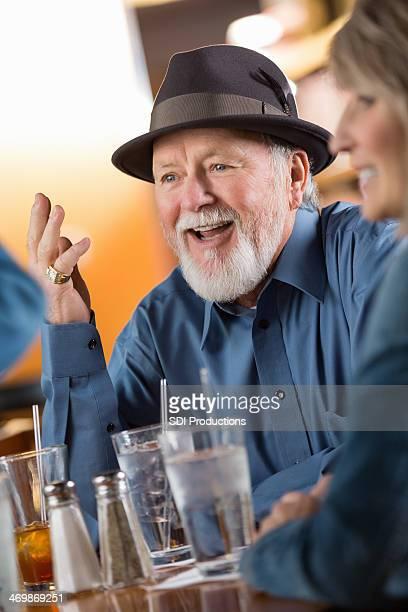 Alter Mann spricht mit Freunden in entspannter Atmosphäre restaurant