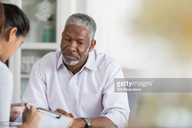 senior man talks to therapist as she takes notes - vulnerability stock pictures, royalty-free photos & images
