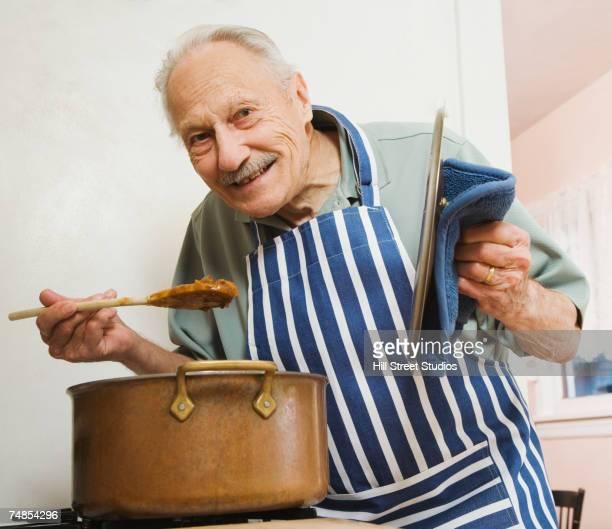 Senior man tasting food in kitchen
