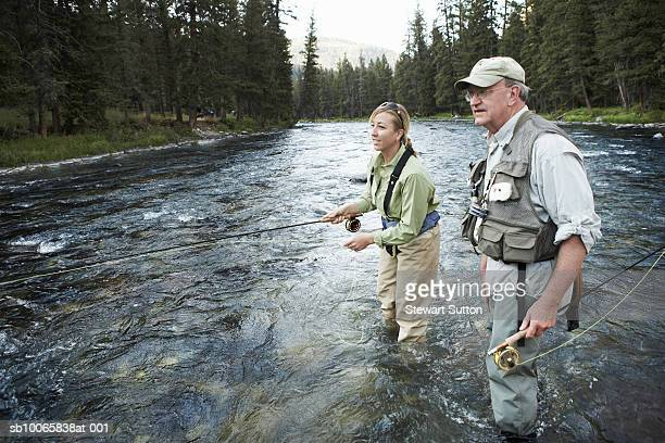 senior man teaching woman fly-fishing - fly casting stock pictures, royalty-free photos & images
