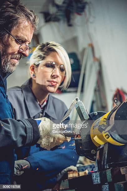 Senior Man Teaching Young Woman How to Grind Metal