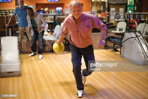 senior man ten-pin bowling - bowling alley stock pictures, royalty-free photos & images