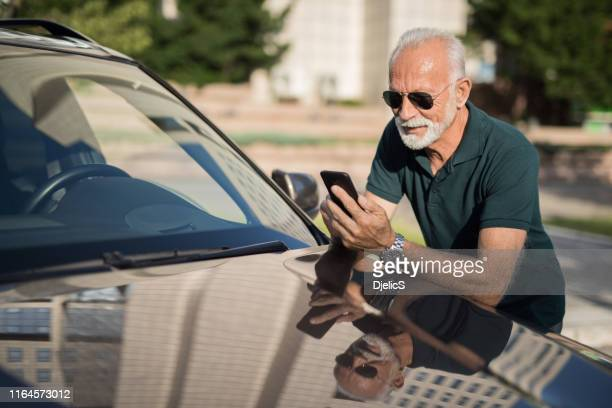 senior man texting a message while leaning on his car. - car insurance stock pictures, royalty-free photos & images