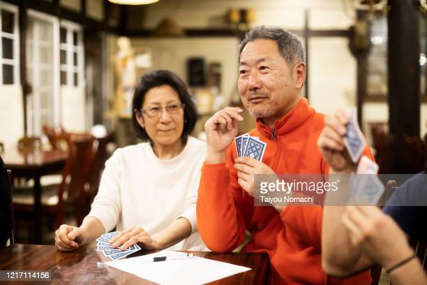 senior man thinking about strategy while playing cards - thinking of you card stock pictures, royalty-free photos & images