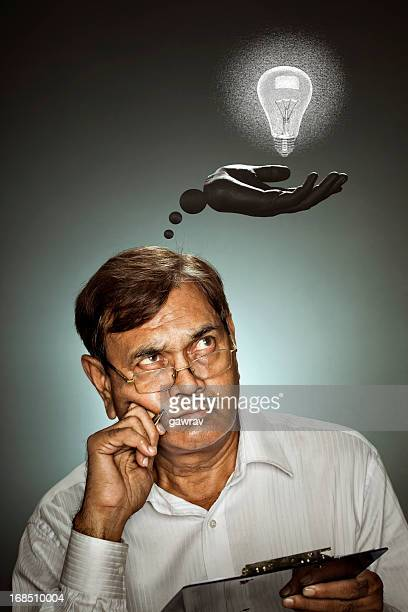 senior man thinking idea by holding a pen and clipboard - authors stock photos and pictures