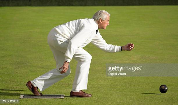 Senior Man Throwing a Bowling Ball on a Bowling Green