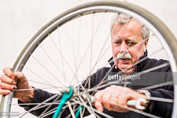 senior man tightening bicycle tire outside workshop - tighten stock photos and pictures