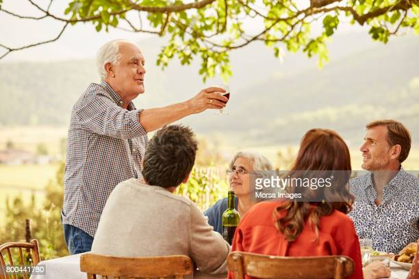 senior man toasting wine to family during lunch - cinco pessoas imagens e fotografias de stock