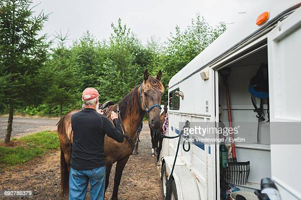 Senior Man Touching Horse Tied To Horse Trailer On Road