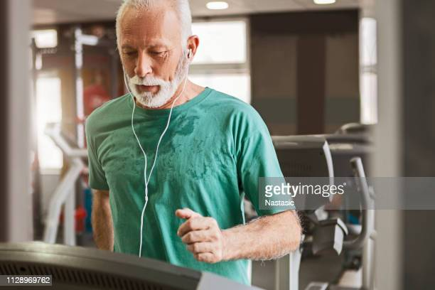 senior man training cardio on a treadmill - treadmill stock pictures, royalty-free photos & images