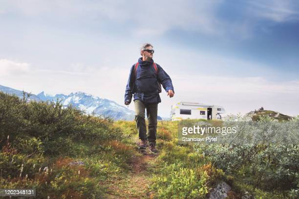 Senior man traveling with backpack, campervan and mountains in background