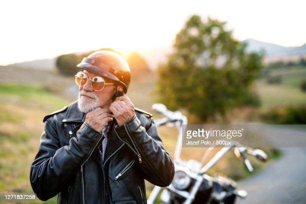 a senior man traveller with motorbike in countryside, putting on helmet - blouson en cuir photos et images de collection