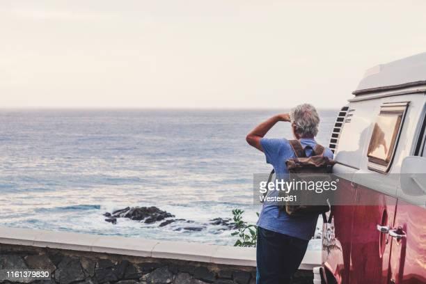 senior man travelling in a vinatge van, looking at the sea, rear view - un solo hombre fotografías e imágenes de stock