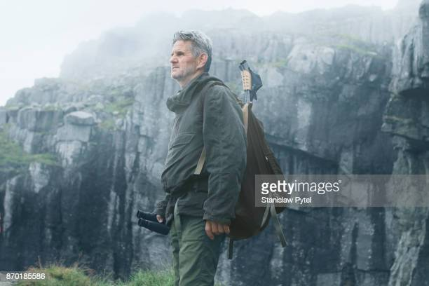Senior man trekking in mountains, foggy weather
