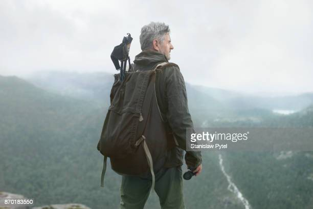Senior man trekking in mountains with backpack and binocular