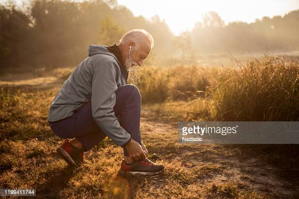 senior man tying shoelaces on sports sneakers - tying shoelace stock pictures, royalty-free photos & images