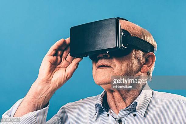 Senior hombre utiliza VR gafas y ajusta el contenido con la mano