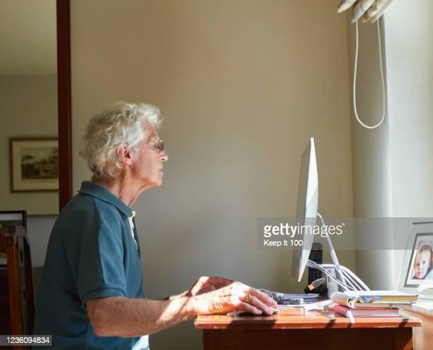 senior man using a computer - senior men stock pictures, royalty-free photos & images