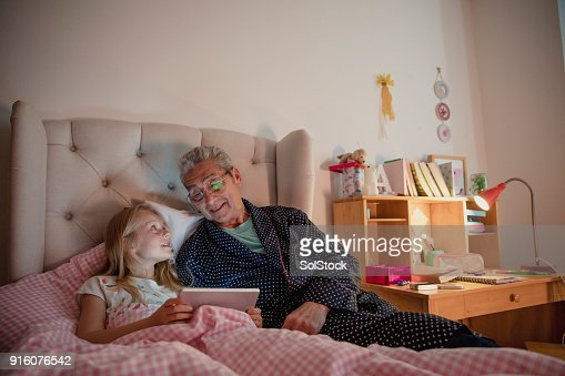 Senior Man Using a Digital Tablet with his Granddaughter