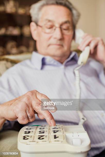 senior man using a landline phone - telephone number stock pictures, royalty-free photos & images