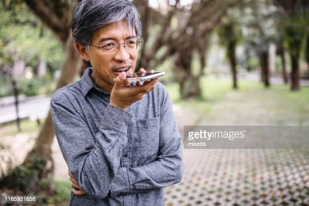 senior man using a phone - voce foto e immagini stock