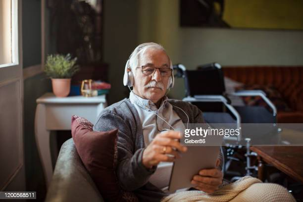 senior man using a tablet at home - senior adult stock pictures, royalty-free photos & images