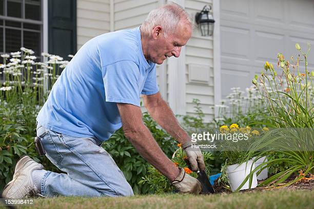 Alter Mann mit einer Kelle-Handwerk und Garten in seinem flower garden