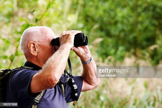 Senior man using binoculars while hiking