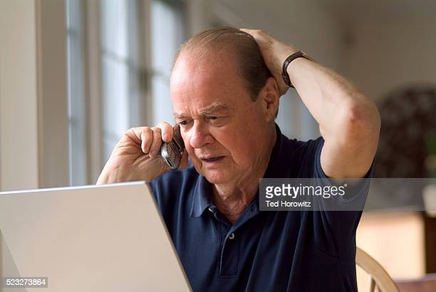 Senior Man Using Cell Phone and Laptop