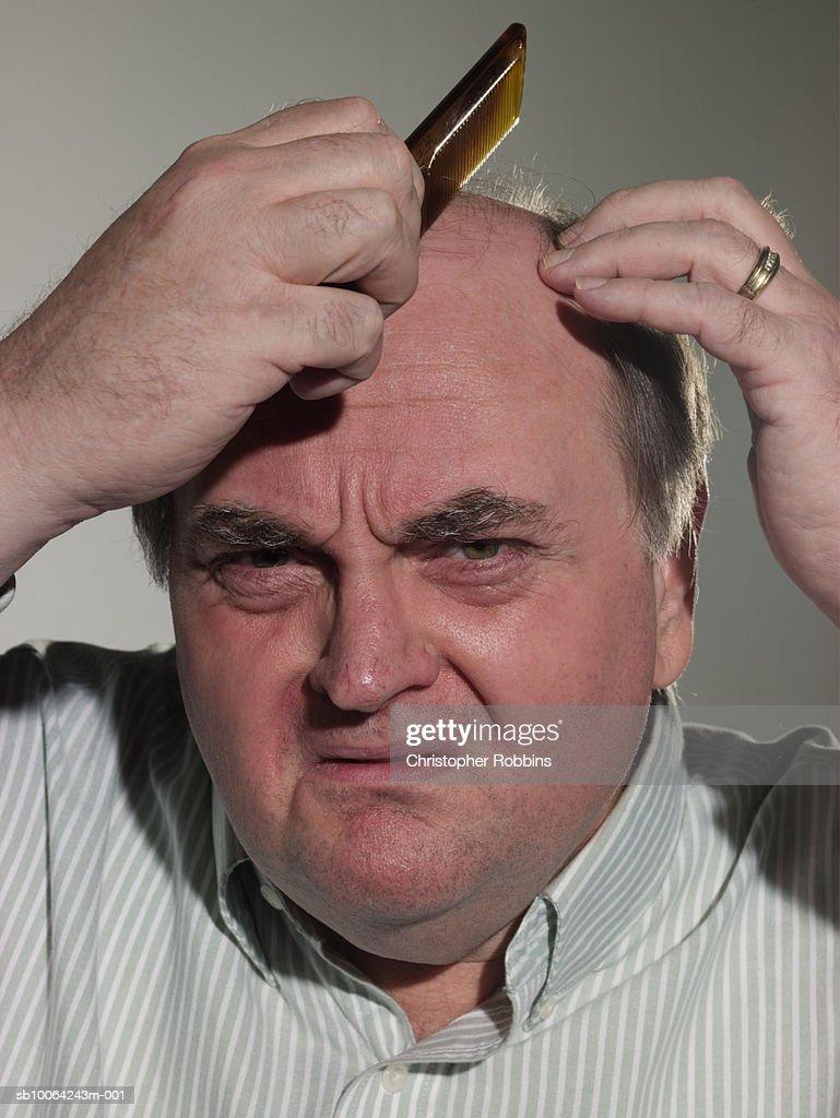 Senior man using comb on bald head, portrait, close-up : Stock Photo