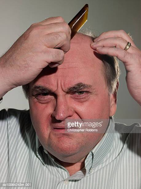 senior man using comb on bald head, portrait, close-up - ugly bald man stock photos and pictures