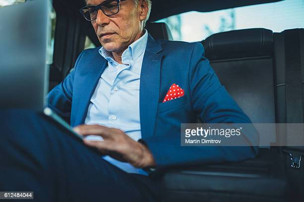 Senior man using computer in taxi