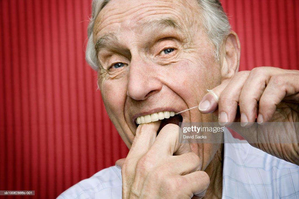 Senior man using dental floss to clean teeth, close-up : Stock-Foto