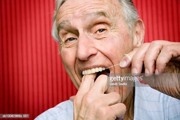 Senior man using dental floss to clean teeth, close-up