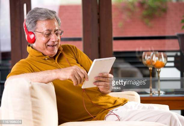senior man using digital tablet and headphones - senior adult stock pictures, royalty-free photos & images