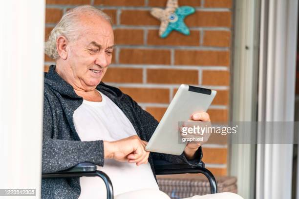 senior man using digital tablet at home - persons with disabilities stock pictures, royalty-free photos & images
