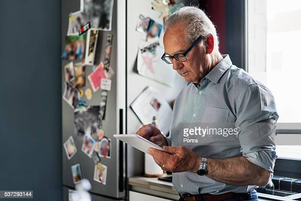 Homme Senior à l'aide de tablette numérique dans la cuisine