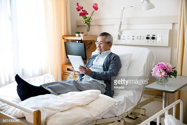 Senior man using digital tablet on bed in hospital