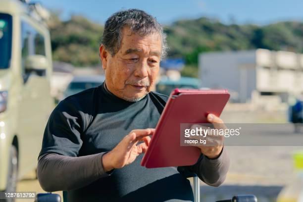 屋外でデジタルタブレットを使用するシニアマン - ポジティブなボディイメージ ストックフォトと画像