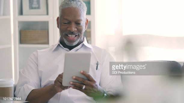 senior man using digital tablet - virtual meeting stock pictures, royalty-free photos & images