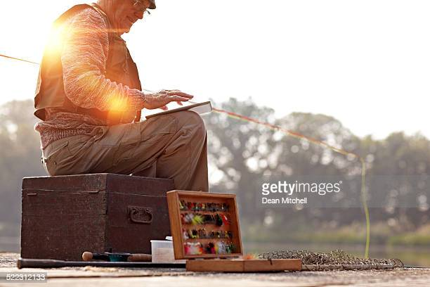 Senior man using digital tablet while fishing