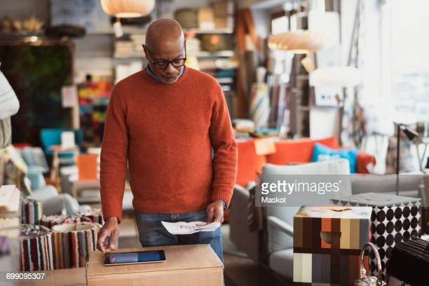 Senior man using digital tablet while reading document at store