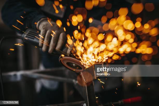 uomo anziano che usa smerigliatrice elettrica in officina - ferro foto e immagini stock
