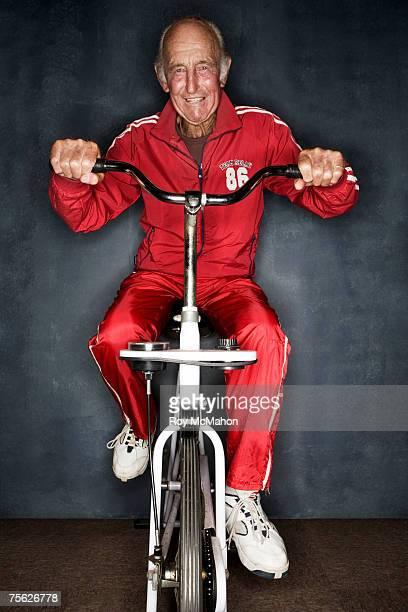 Senior man using exercise bike, front view, portrait