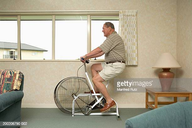 Senior man using exercise bike, side view